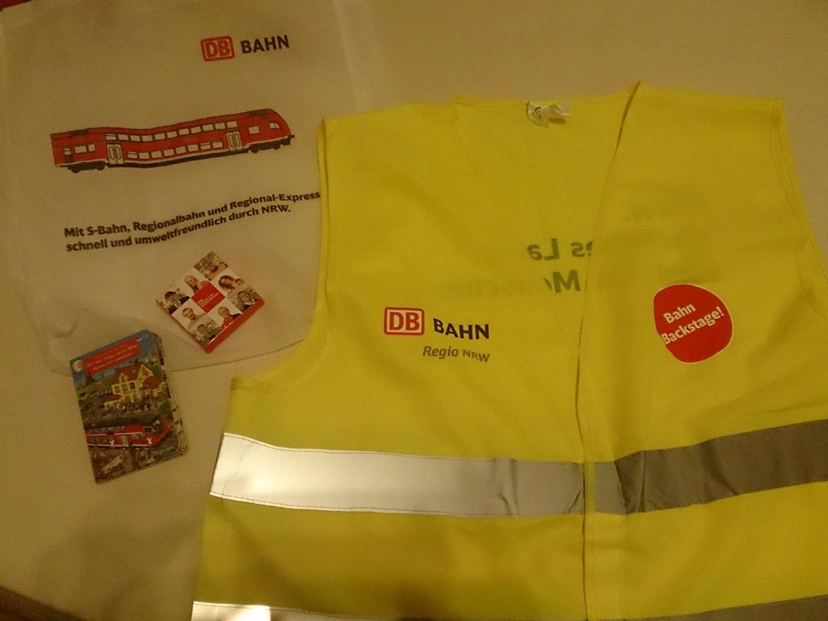 Unser Carepaket mit DB-Sicherheitsweste, Schokolade und Kinderbuch.