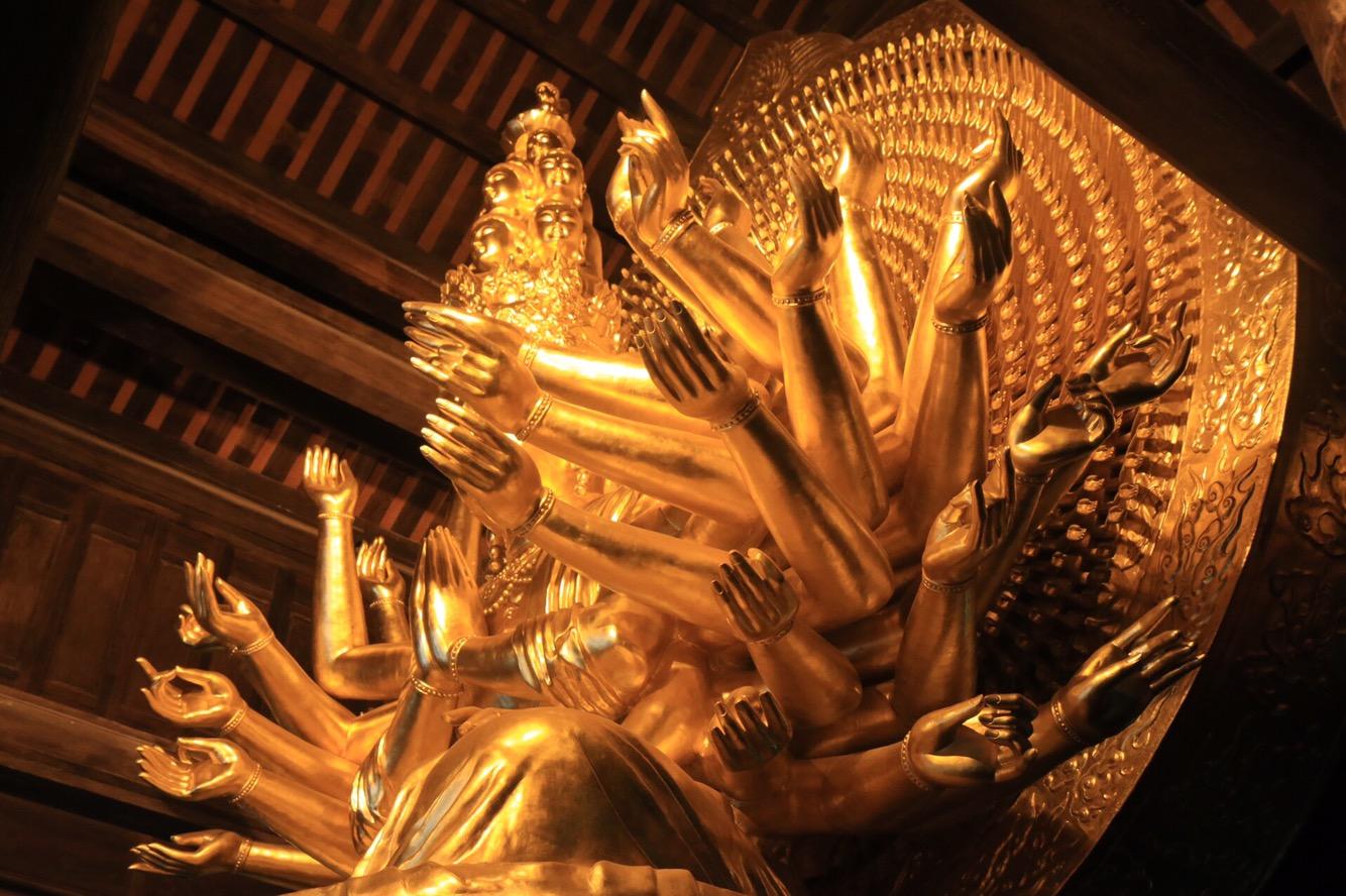 Im Inneren der Haupthalle ein vielarmiger Buddha.
