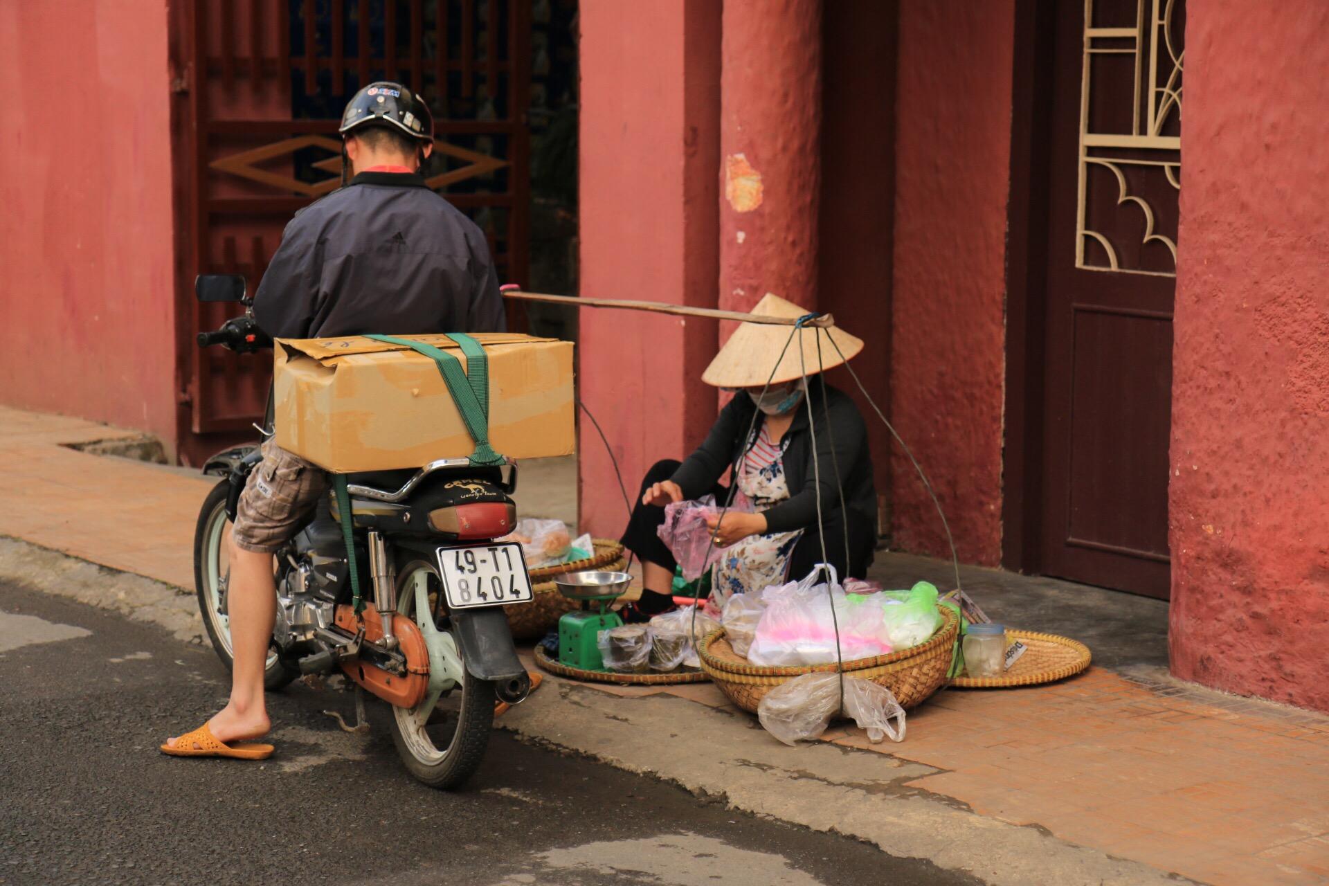 Vietnam-Symbolbild Nummer 1 - alles drauf: Kegelhut, Tragestange und Moped.