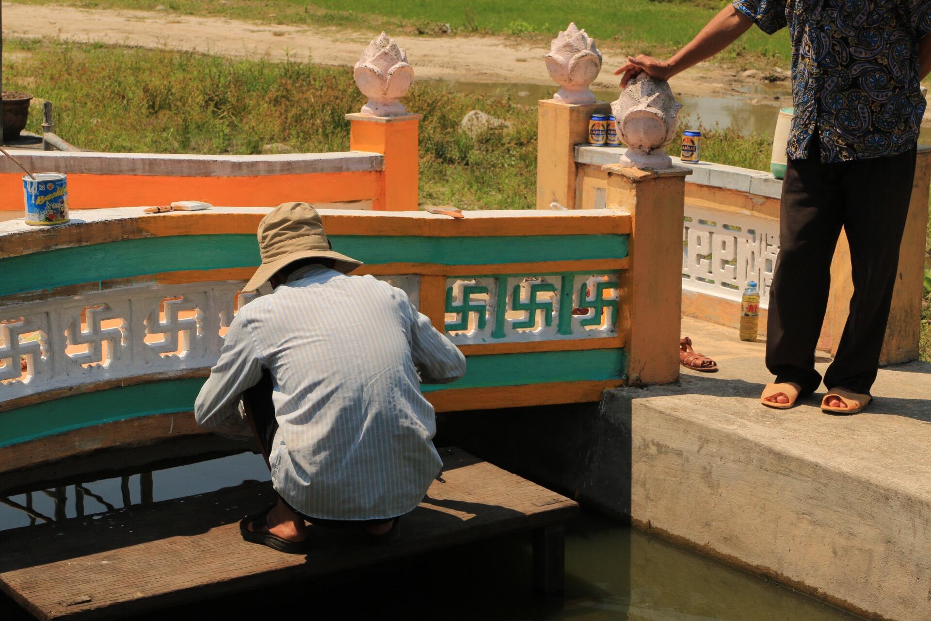 Dieser Handwerker malt natürlich keine Hakenkreuze an den Tempel sondern Swastika - ein religiöses Glückssymbol im Buddhismus.