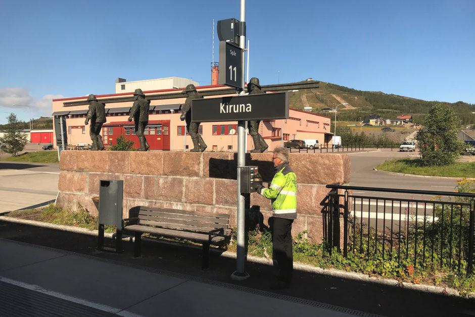 Hier unser Zugchef bei der Abfertigung des Zuges. Im Hintergrund ein Denkmal, das an den Bau der Strecke erinnert.