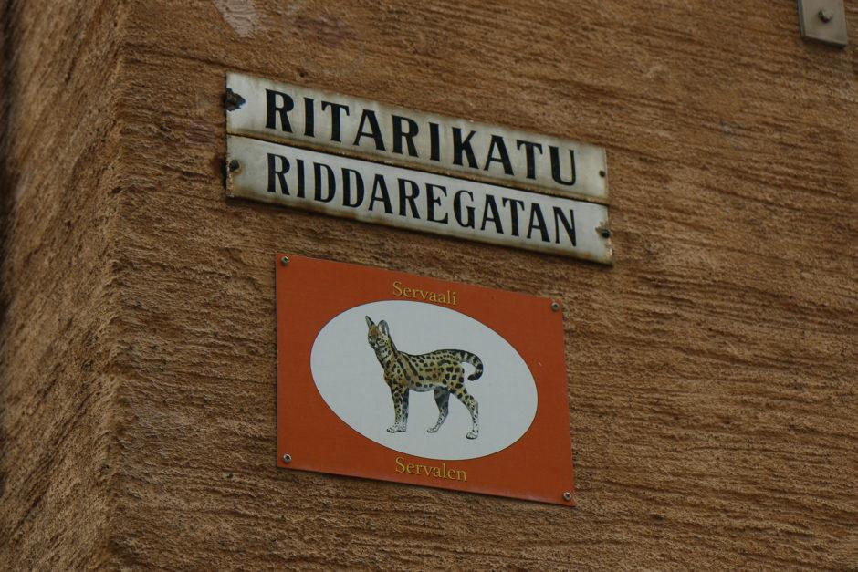 Eins der zweisprachigen Straßenschilder. Und weil früher nicht alle lesen konnte, hatten Straßen zusätzlich noch Tierbilder.