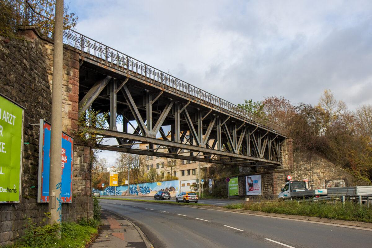 Am Ortschild von der A671 kommend überquert diese schöne Eisenbrücke die Schnellstraße.